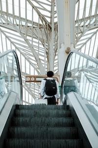 man in black jacket and blue denim jeans standing on escalator
