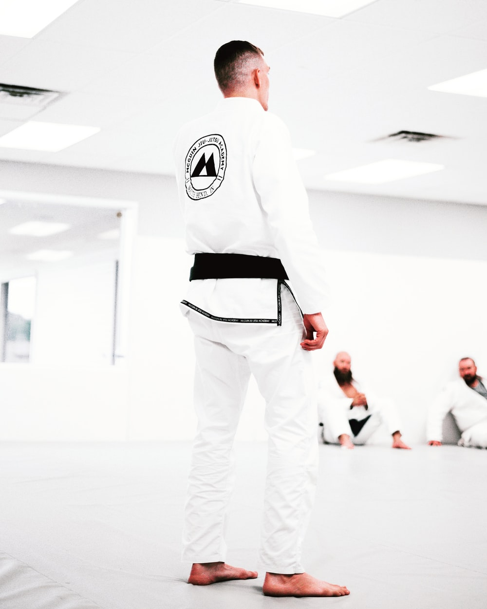 man in white and black adidas long sleeve shirt and white pants standing on white floor