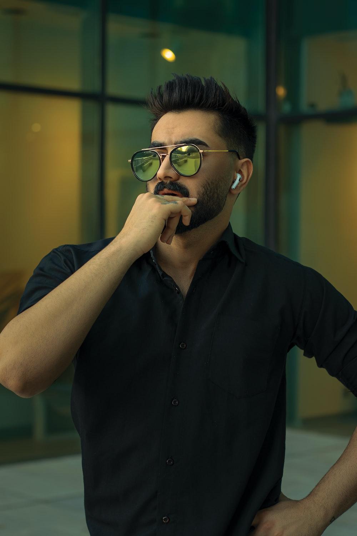 man in black button up shirt wearing black framed eyeglasses
