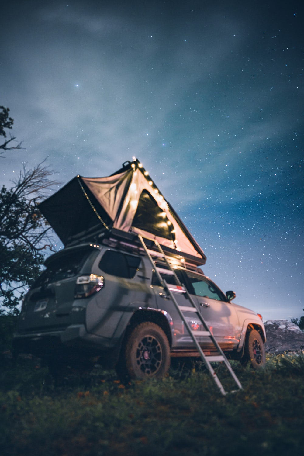 white suv in front of tent during night time