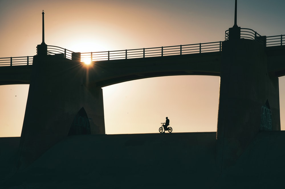 silhouette of 2 people standing on concrete bridge during sunset