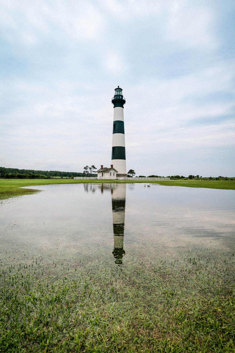 black and white lighthouse near green grass field under white clouds during daytime