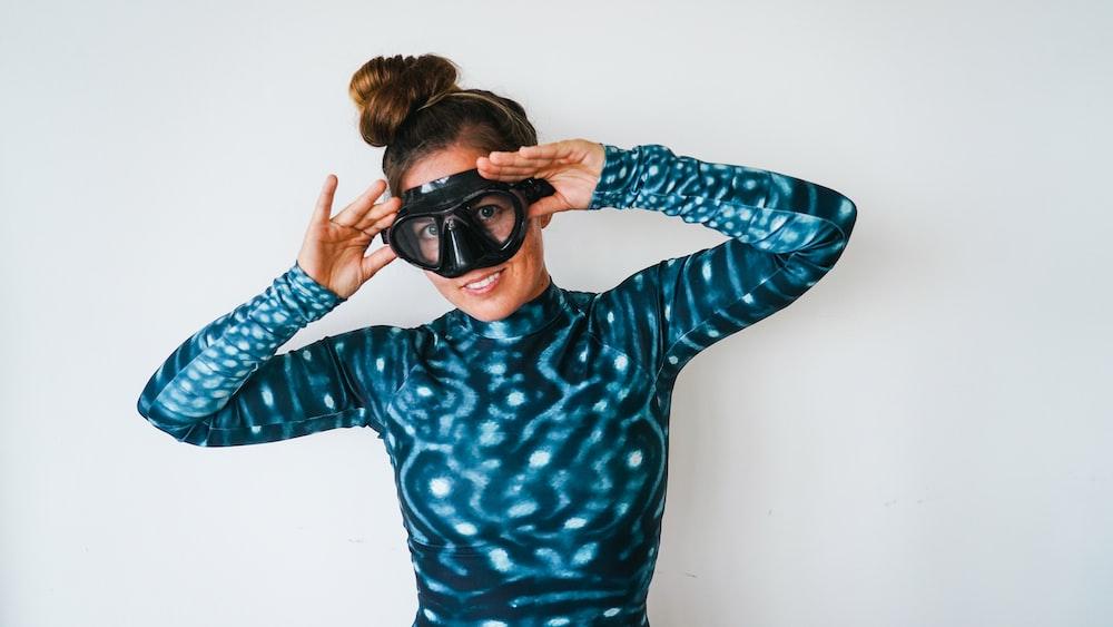 woman in blue and black polka dot long sleeve shirt wearing black sunglasses