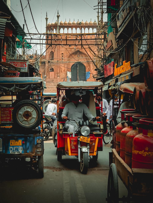 man in black jacket riding red and black auto rickshaw