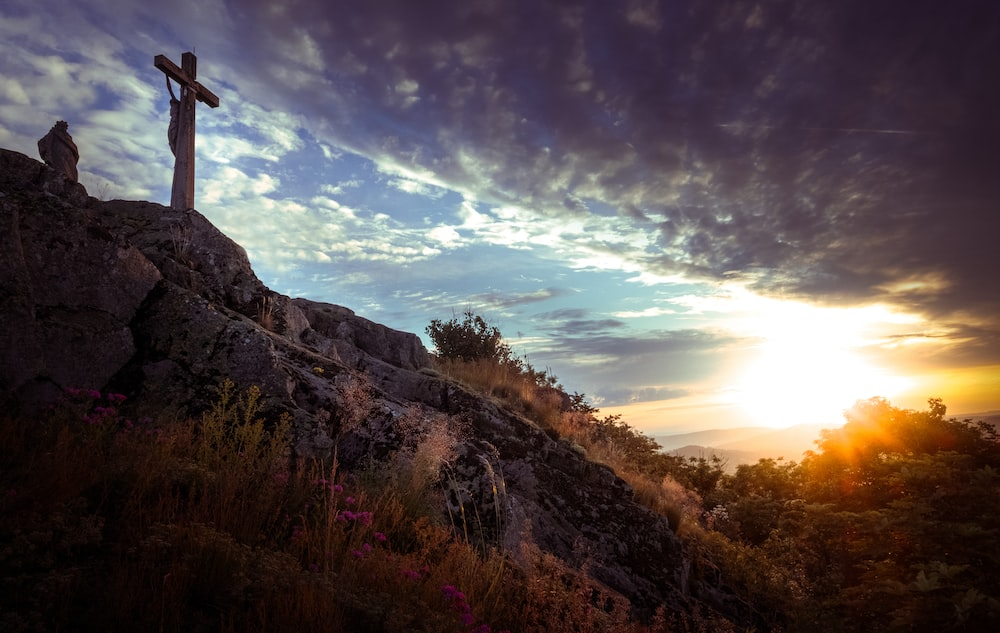 brown wooden cross on top of mountain during daytime