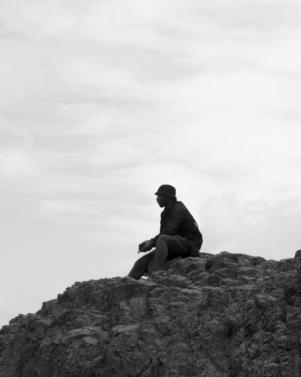 grayscale photo of man sitting on rock
