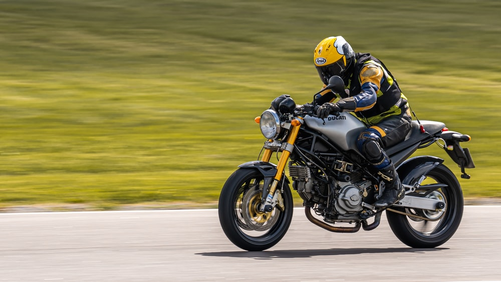 man in yellow helmet riding on black and white sports bike