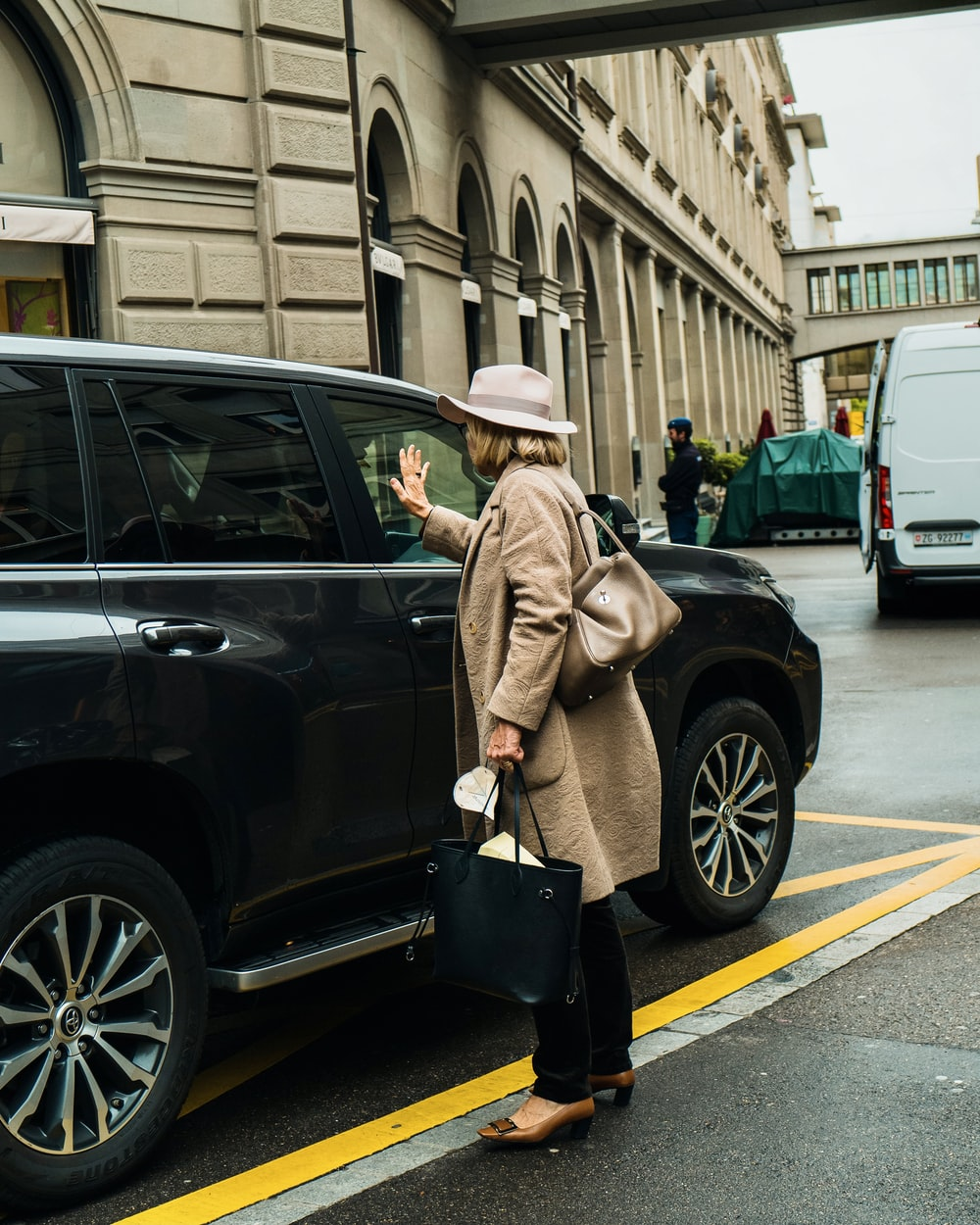 man in brown coat and black hat standing beside black suv during daytime