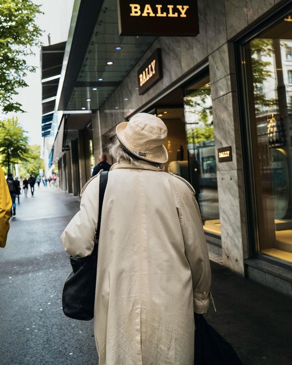 man in beige jacket walking on sidewalk during daytime