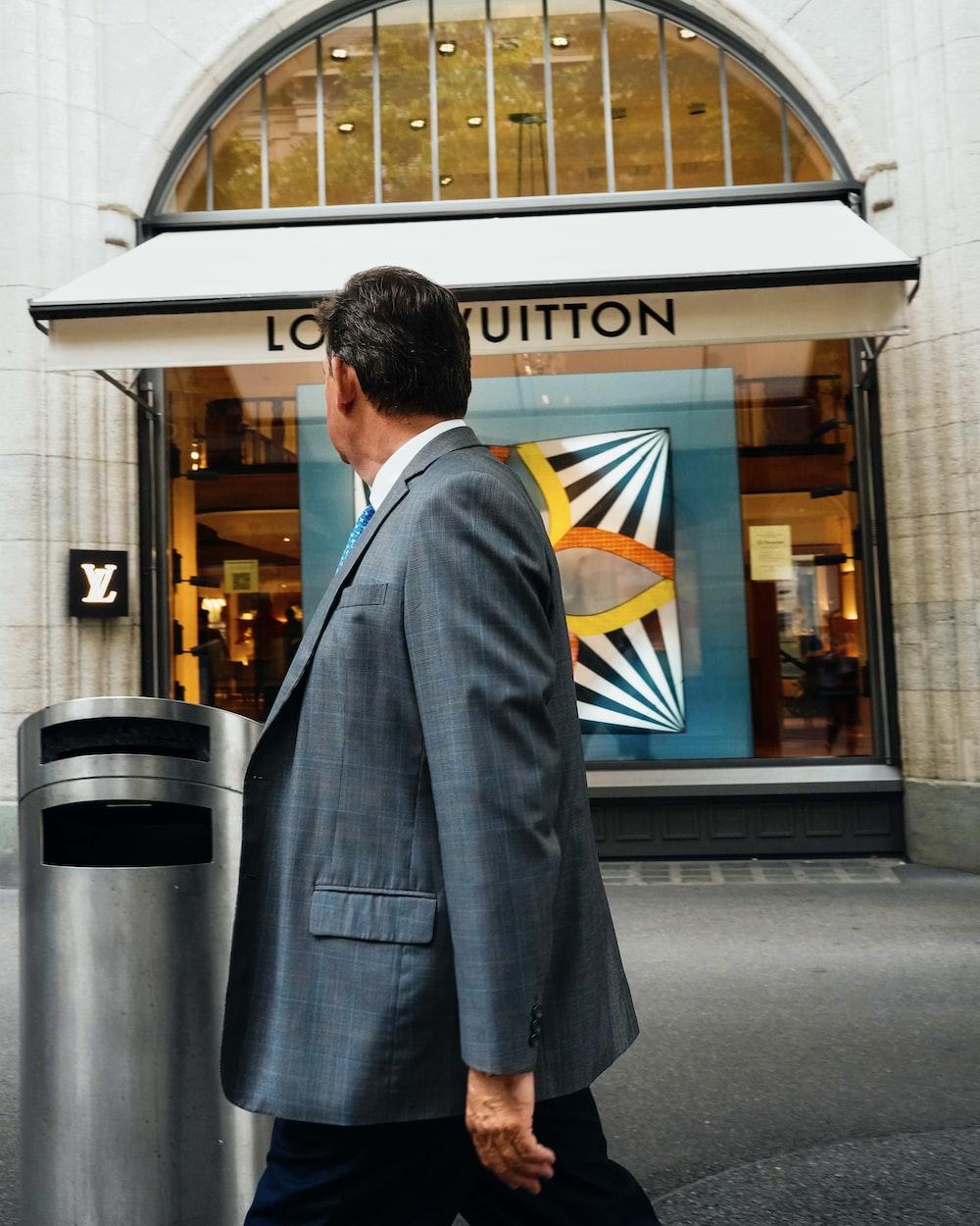 man in black suit standing near gray trash bin