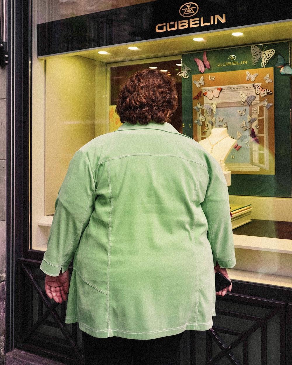 woman in white long sleeve shirt standing near glass door