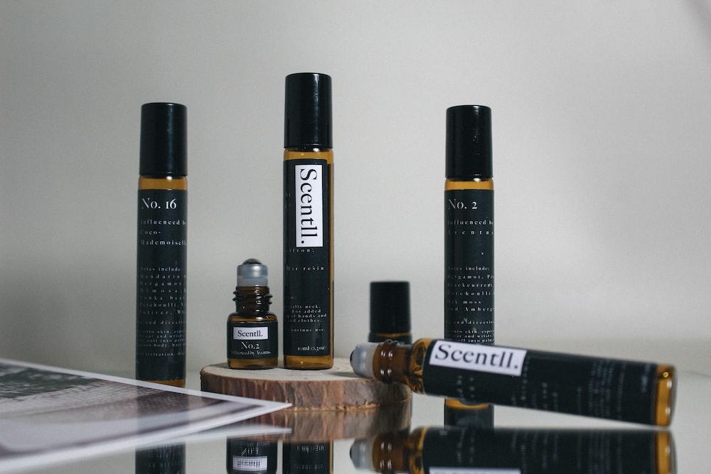 black and brown plastic bottles on brown wooden shelf