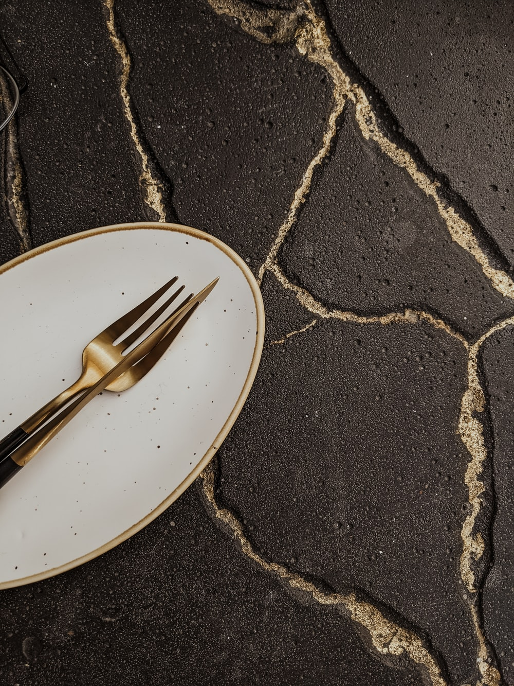 stainless steel fork on white and black ceramic plate