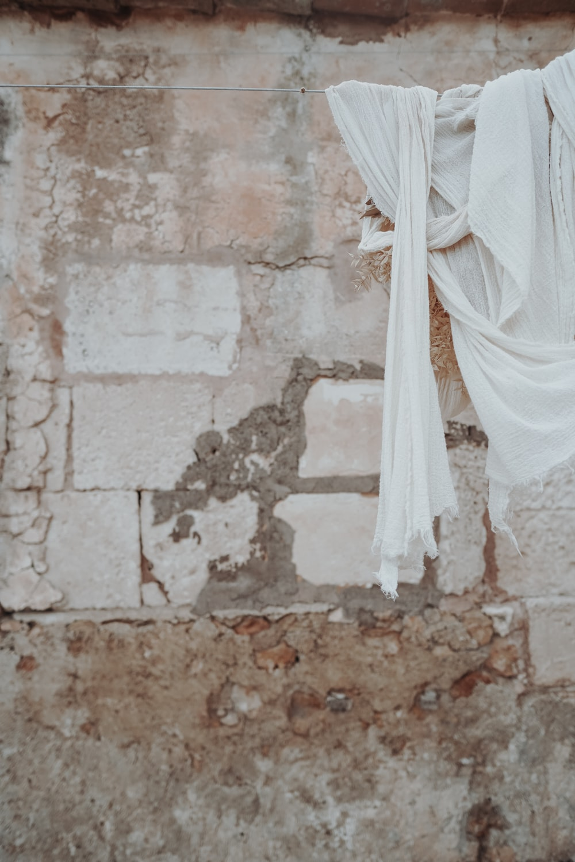 white textile on brown concrete wall