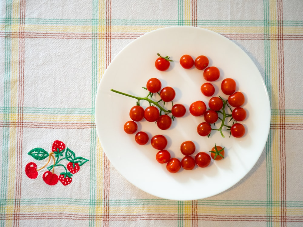 red round fruits on white ceramic plate