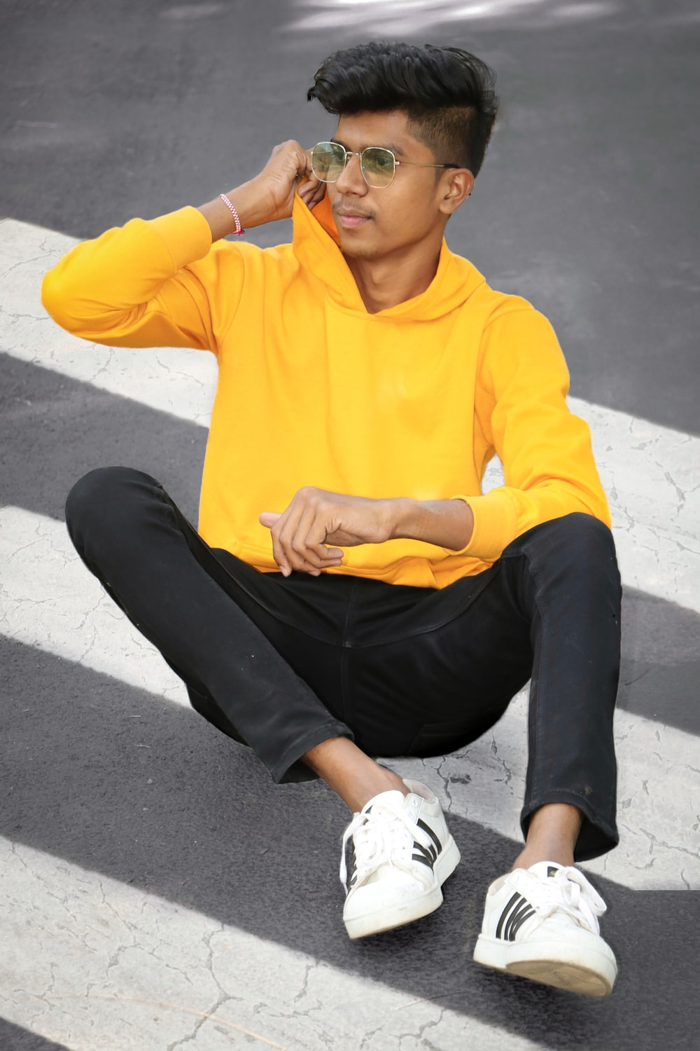 man in yellow hoodie and black pants sitting on gray concrete floor