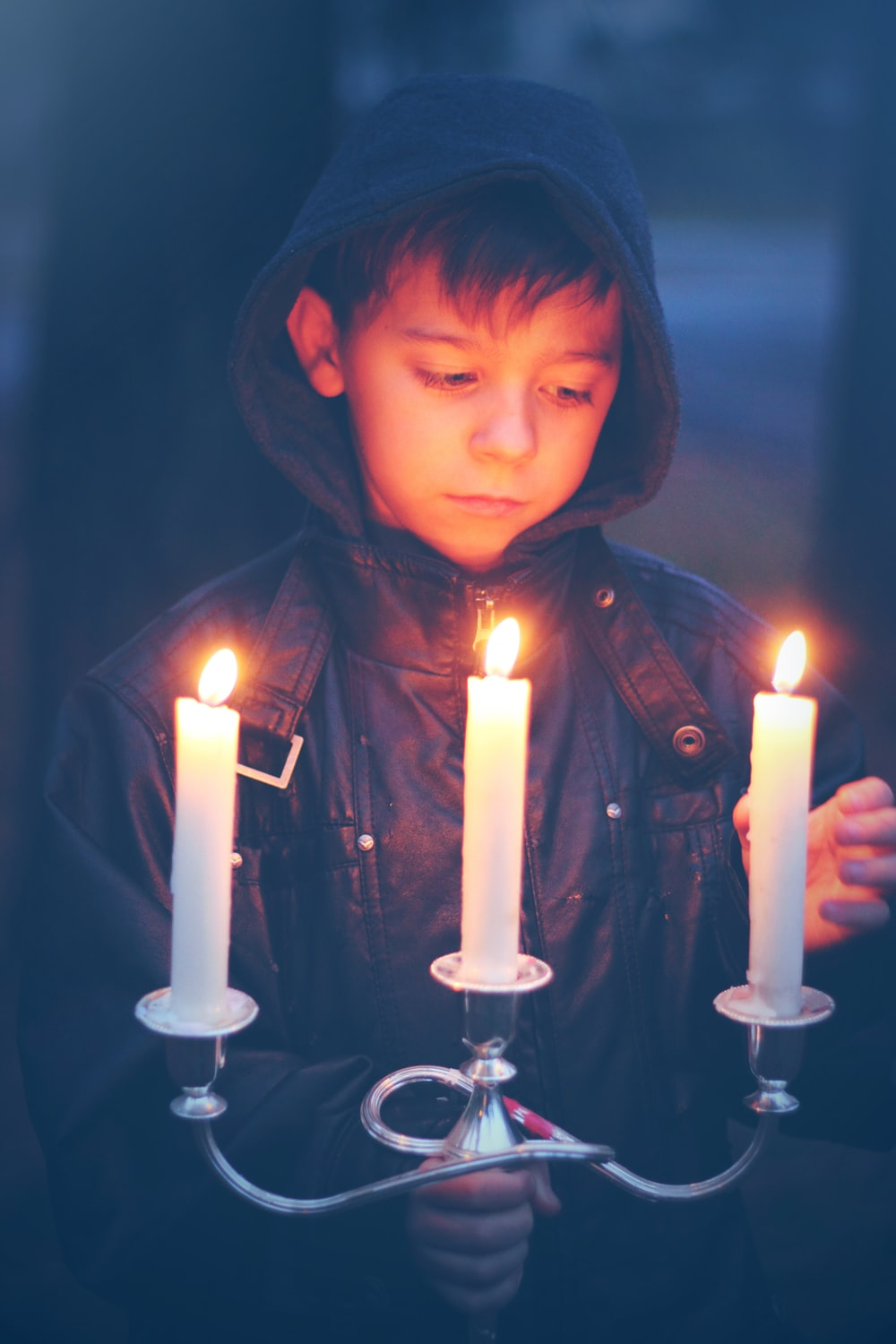 boy in gray hoodie holding lighted candles