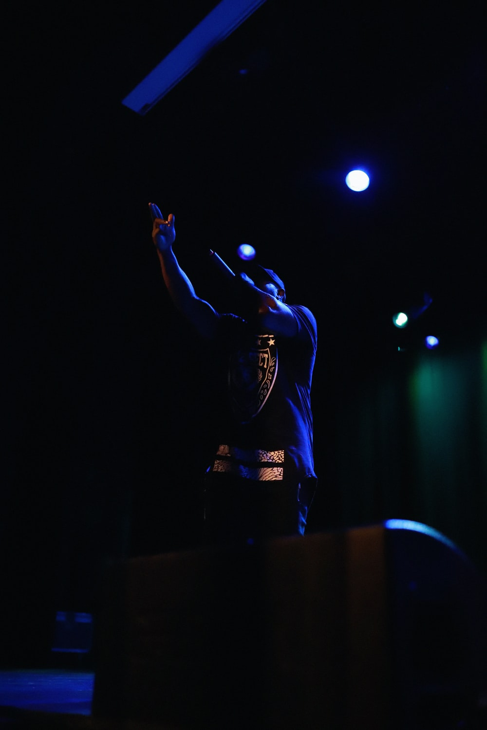man in black long sleeve shirt standing on stage
