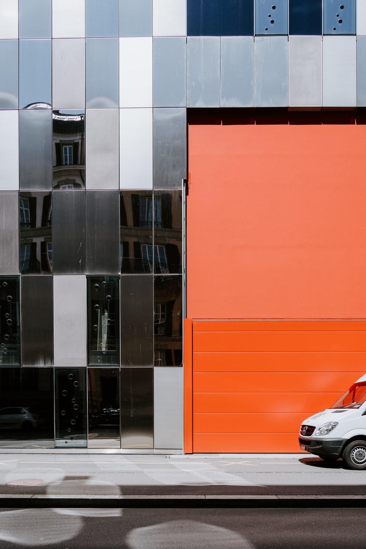 white car parked beside orange wall