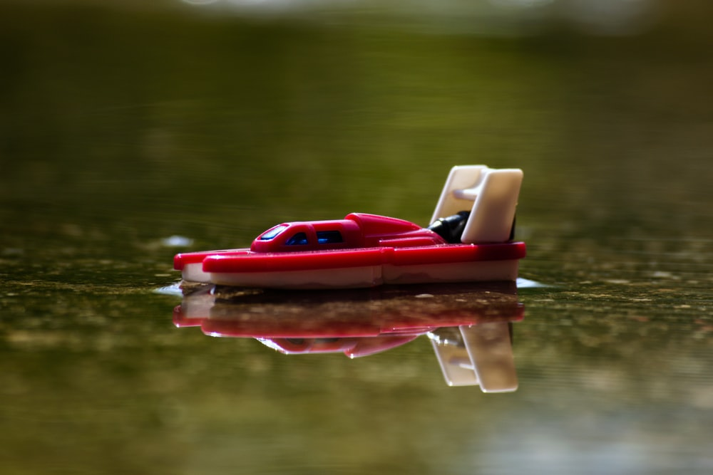 red and white plastic boat on water