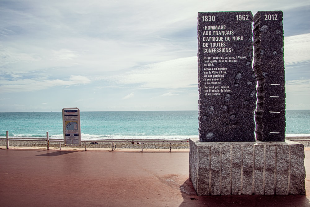 gray concrete post near sea during daytime