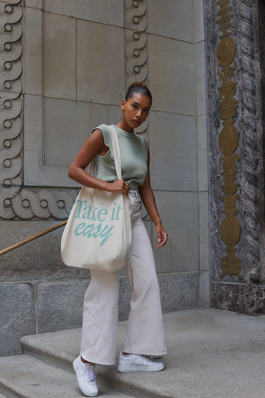 woman in white sleeveless dress standing on gray concrete floor