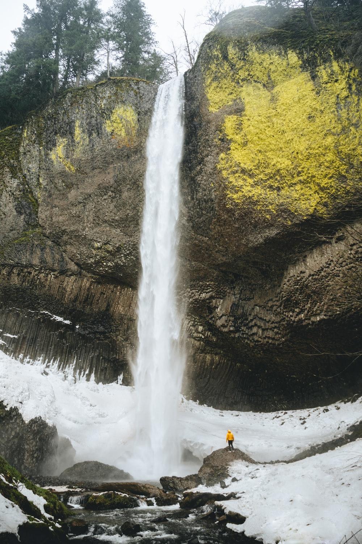 person in orange jacket standing on rock near waterfalls during daytime