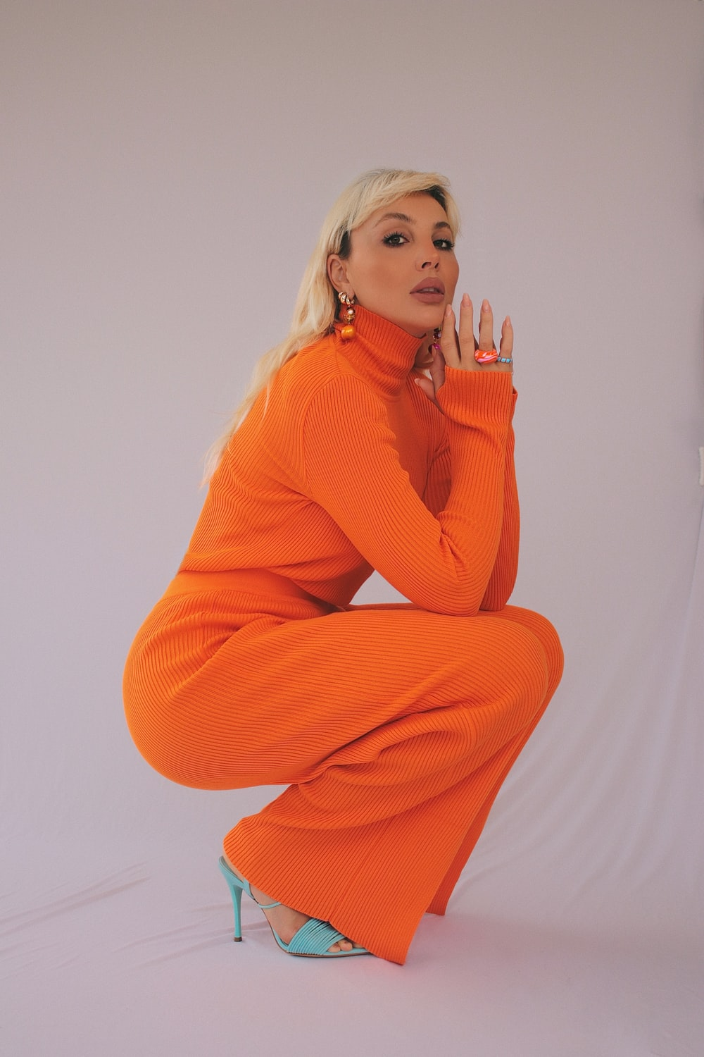 woman in orange sweater and brown pants sitting on white floor