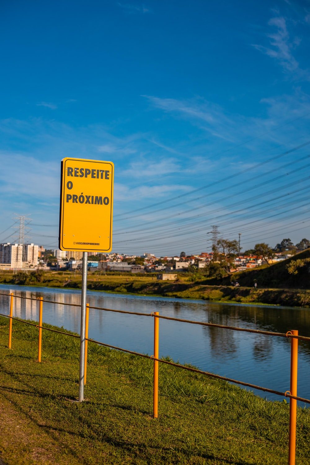 yellow and black road sign near body of water during daytime