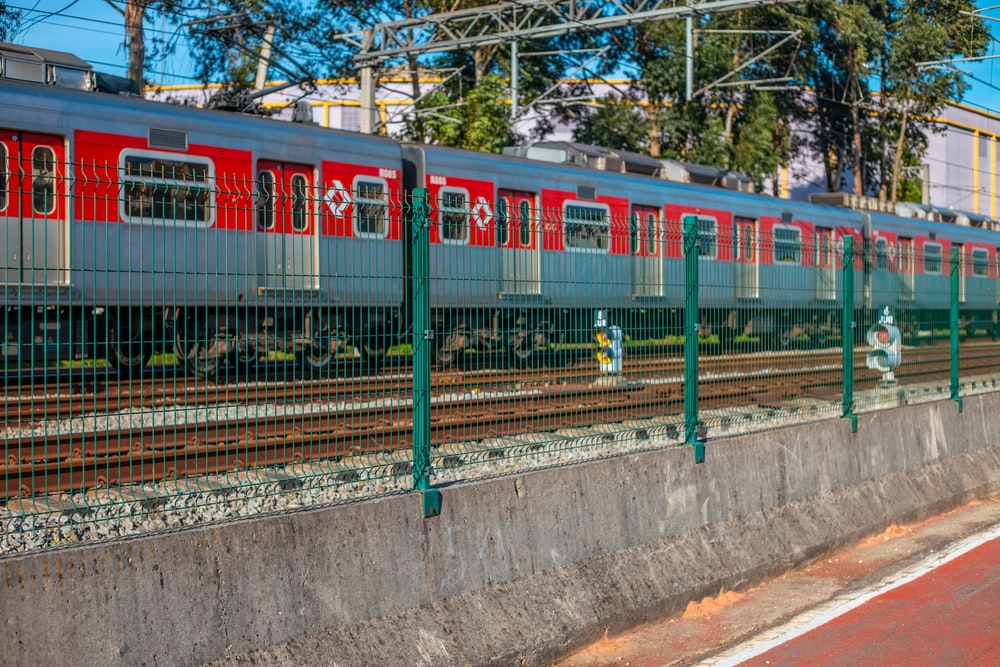 red and green train on rail tracks during daytime