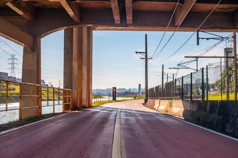 gray concrete road under bridge during daytime