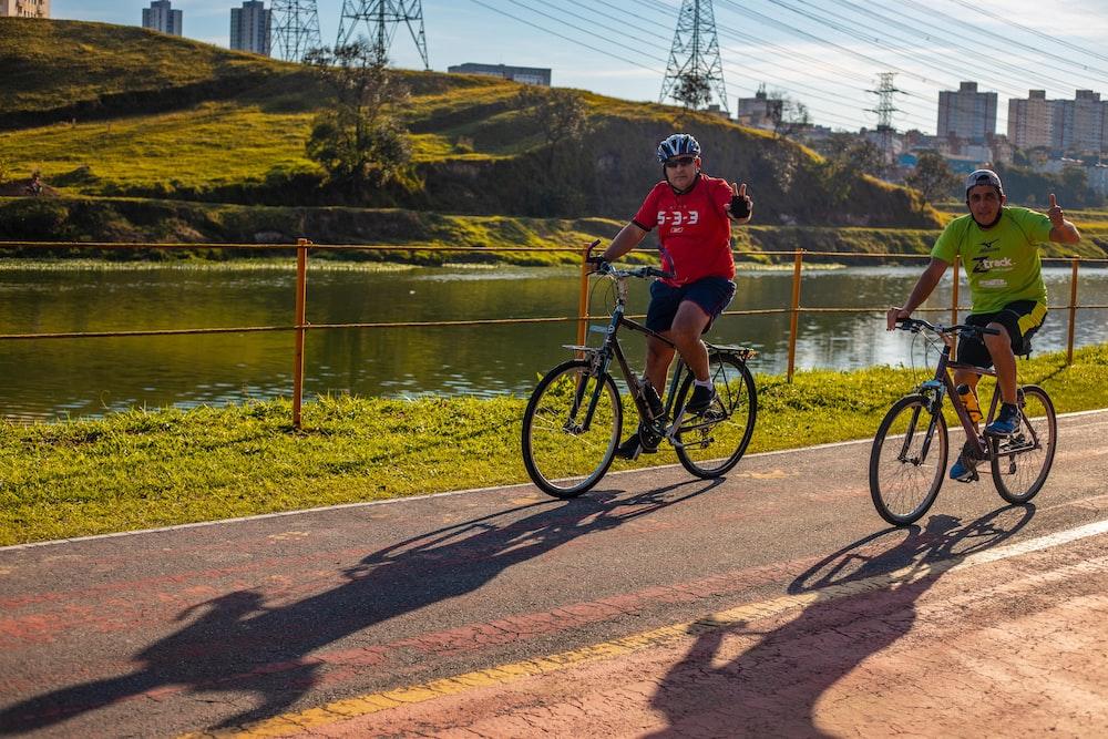 man in red shirt riding bicycle near lake during daytime