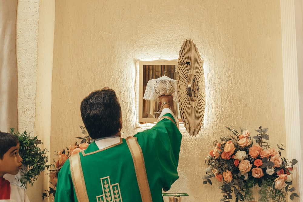 man in green and white shirt standing near wall