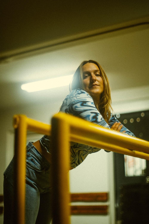 woman in blue denim jacket standing beside yellow metal railings