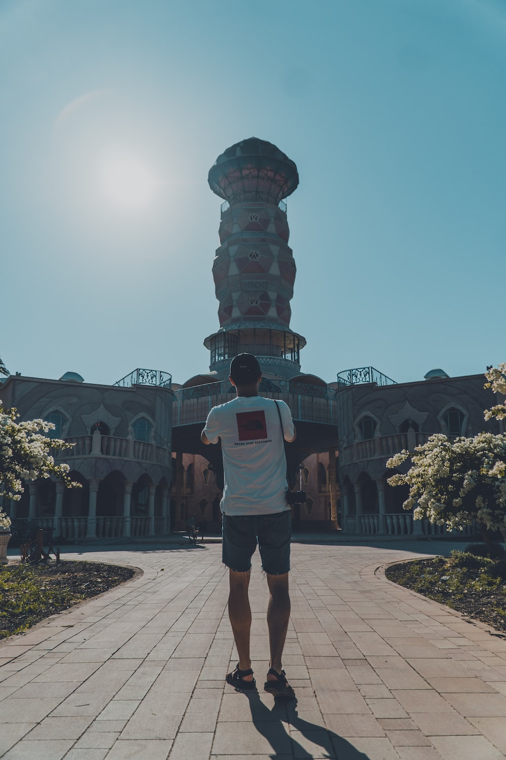 man in white t-shirt and brown shorts standing near brown concrete building during daytime