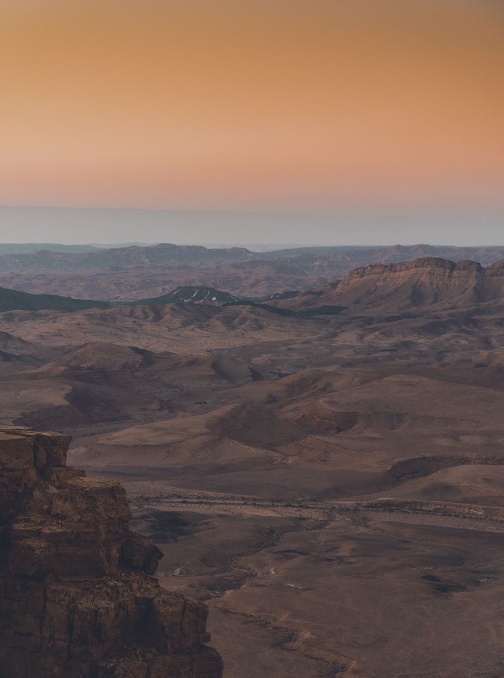 brown rocky mountain under orange sky during daytime