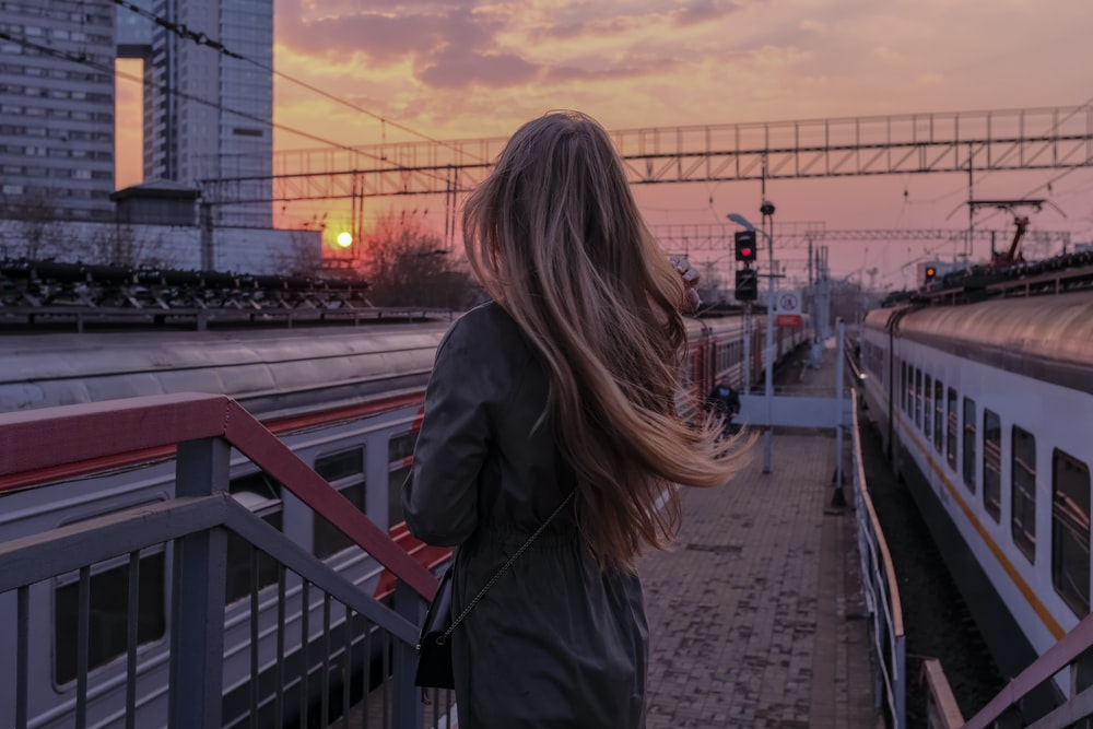 woman in black coat standing on the bridge during sunset
