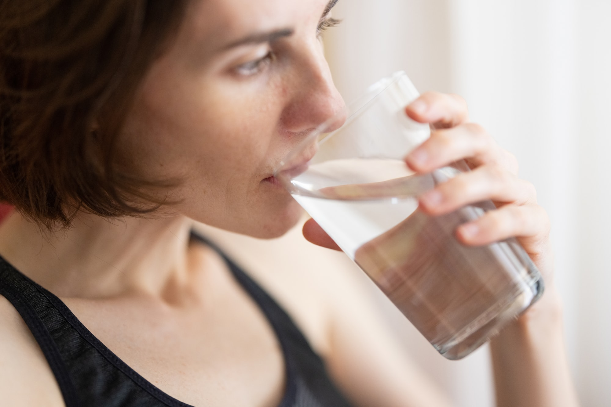 a woman drinking a glass of fresh water
