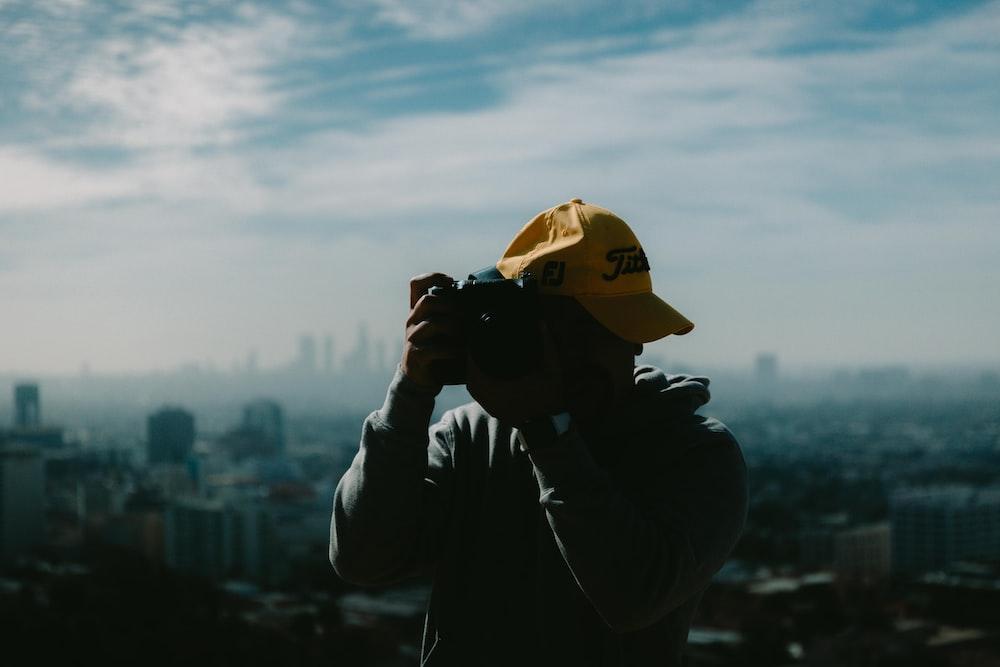 man in black jacket wearing yellow cap holding black dslr camera