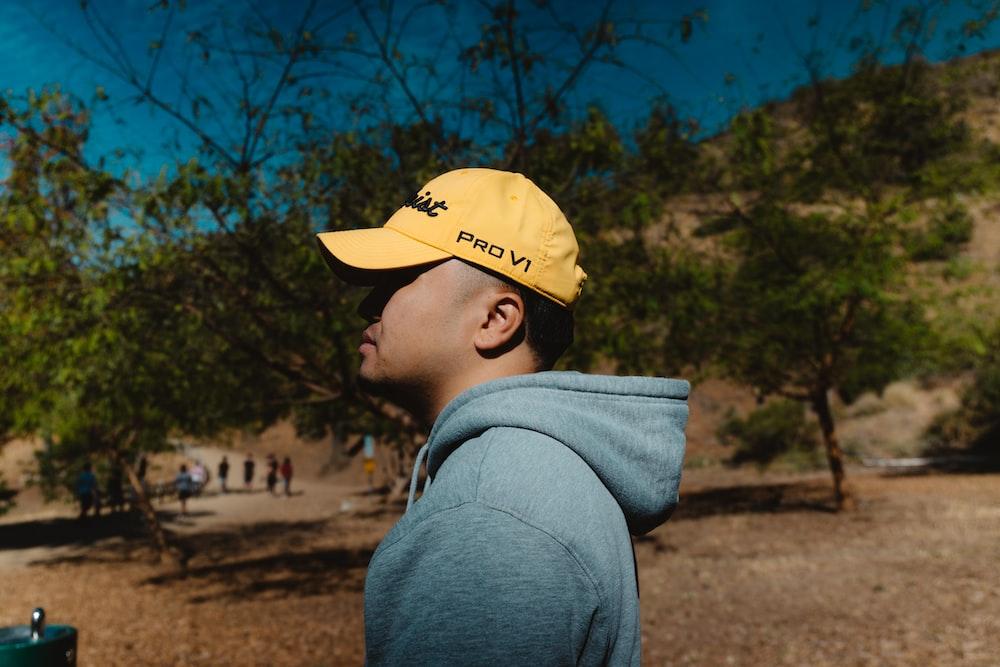 boy in yellow baseball cap and gray hoodie