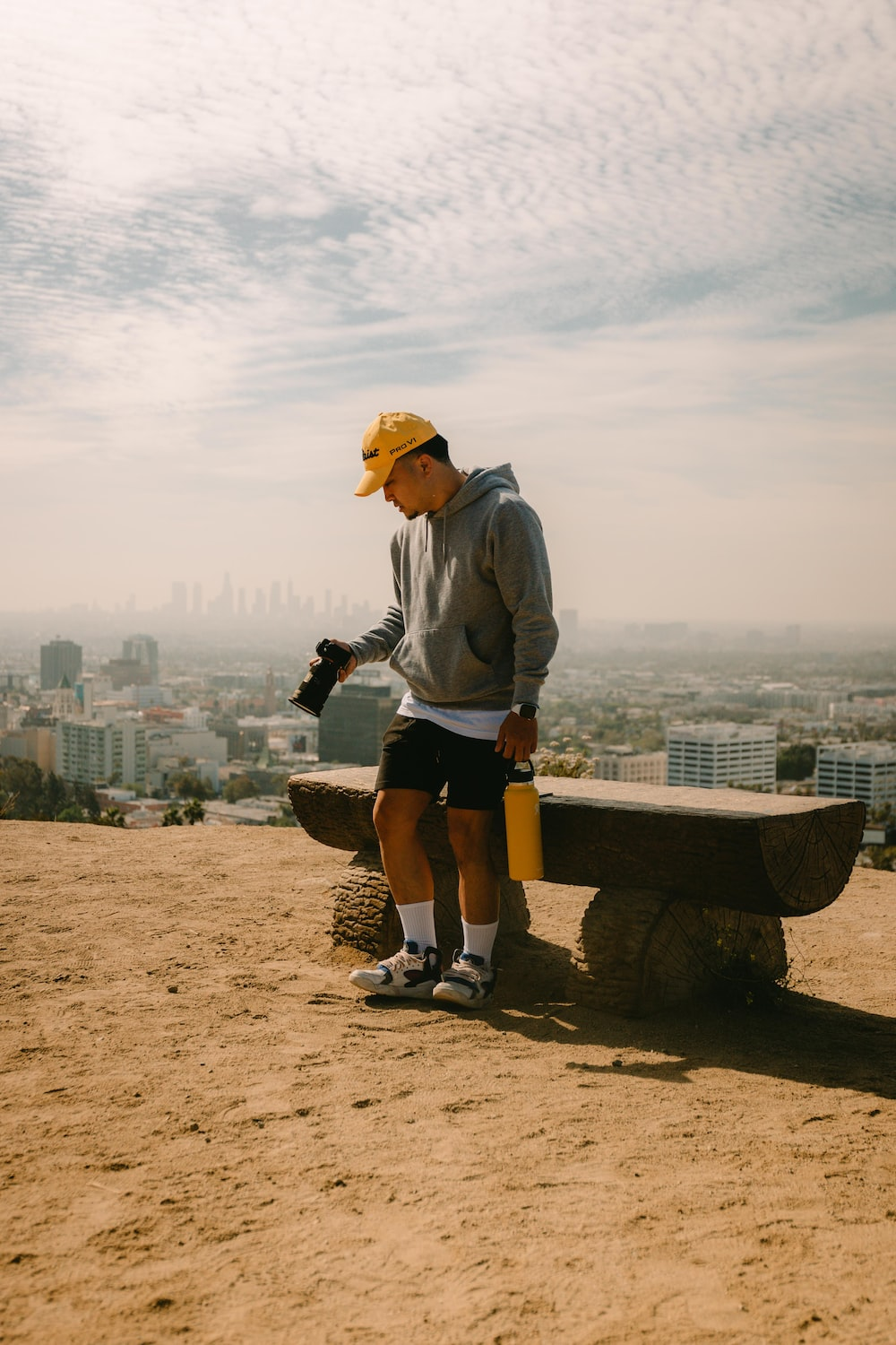 man in gray long sleeve shirt and yellow cap standing on brown wooden bench during daytime