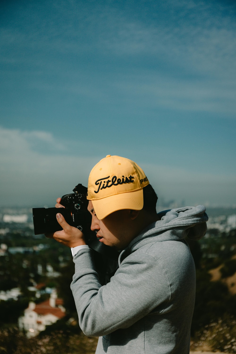 person in yellow cap and gray hoodie holding black dslr camera