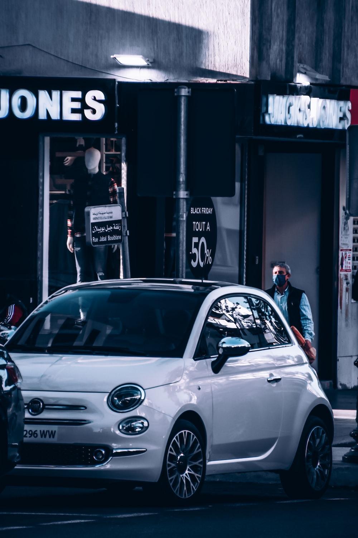 white sedan parked beside black and white building