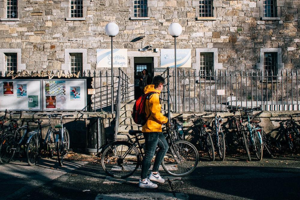 man in yellow jacket riding bicycle