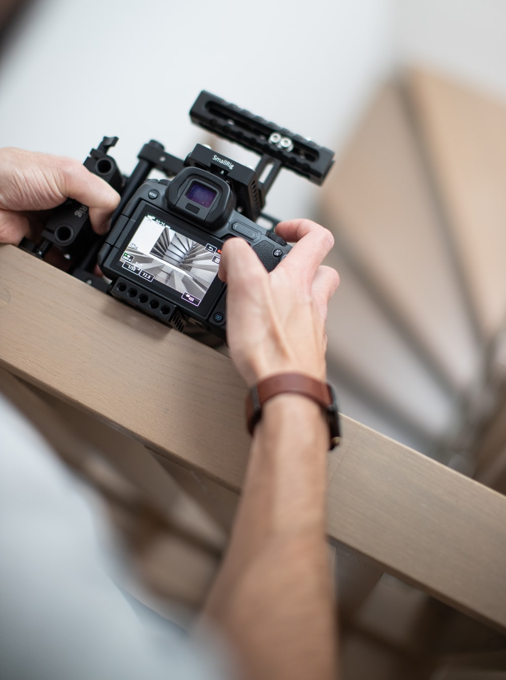 person holding black camera on brown wooden table