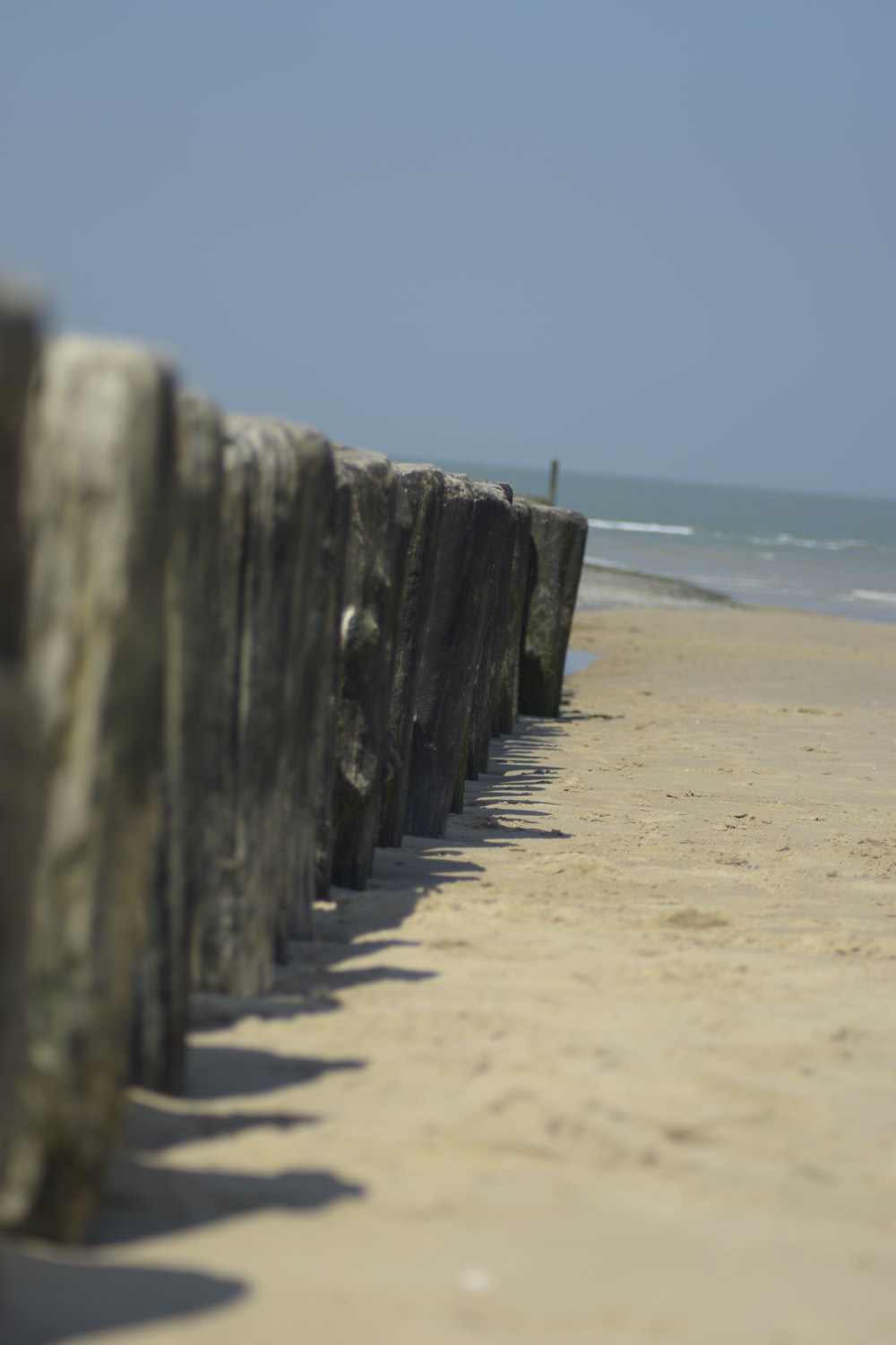 gray wooden fence on beach during daytime