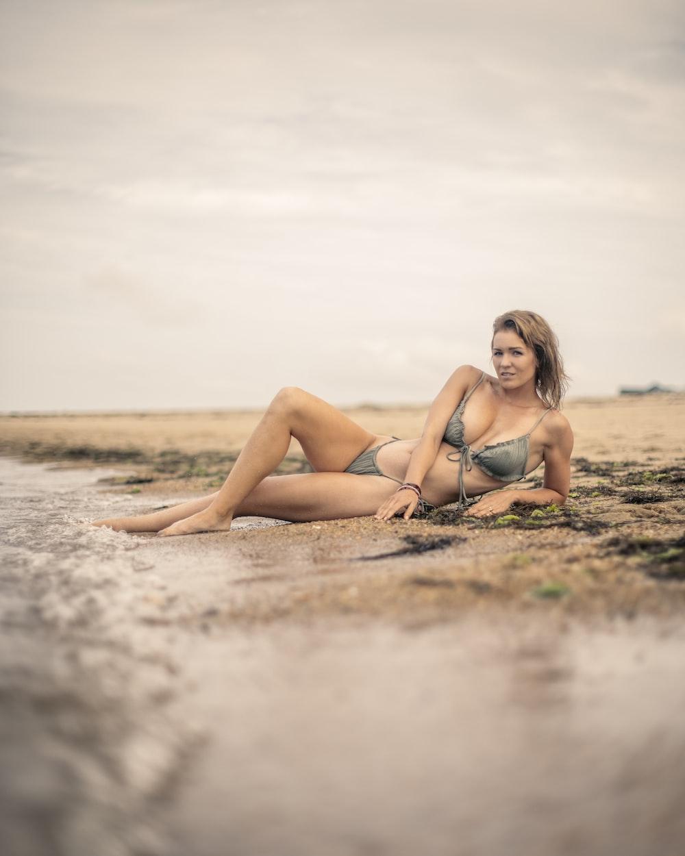 woman in black bikini lying on sand during daytime