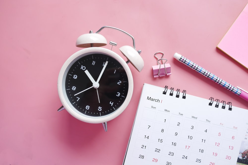 white and pink analog alarm clock