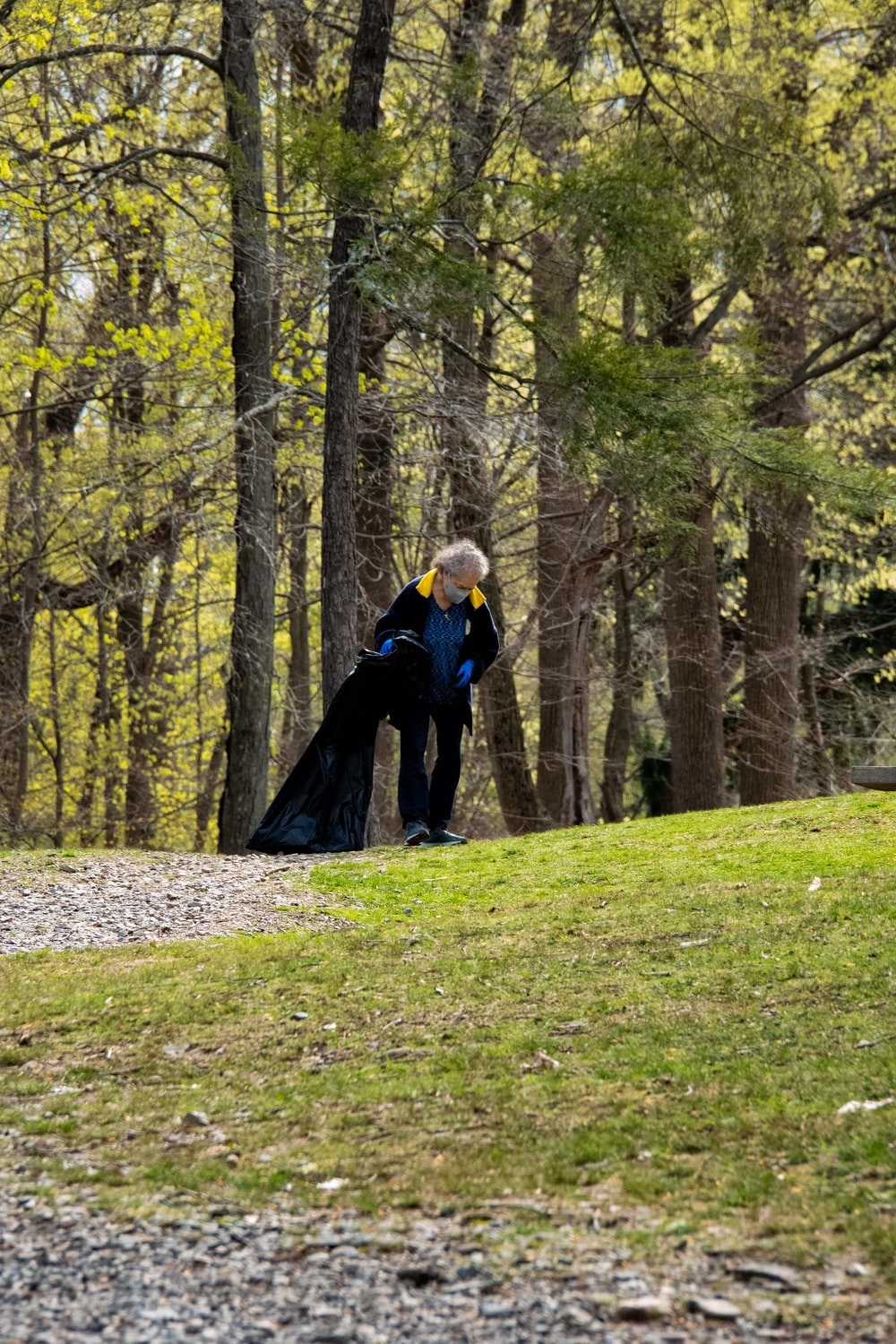 woman in blue jacket standing on green grass field surrounded by trees during daytime