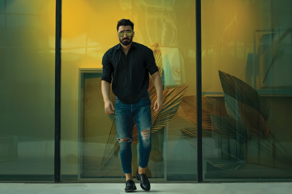man in black polo shirt and blue denim jeans standing beside glass wall